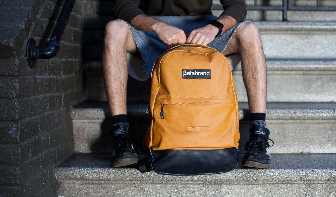 Mustard Yellow Water-Resistant Daypack Backpack on granite stairs in San Francisco between models legs