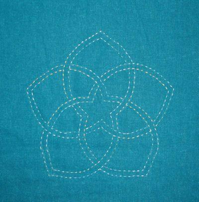 Sashiko Starflower on teal with varigated thread.
