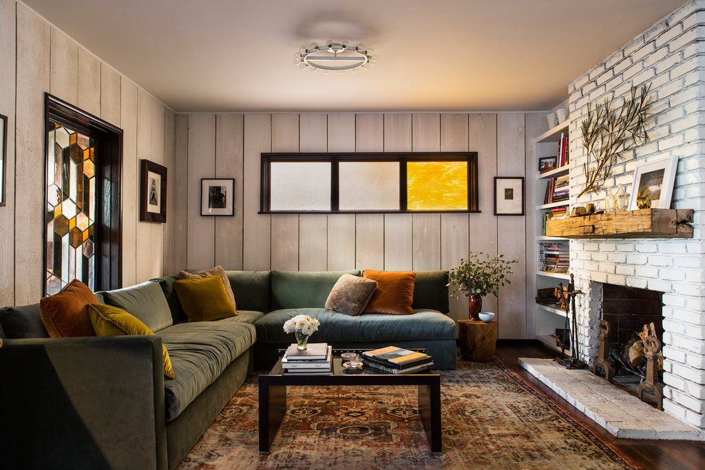 In the living room, a fixture from Rewire hangs overhead. A midcentury wall hanging is mounted on the painted white brick above the mantle, and a custom velvet wraparound couch maximizes seating. The stained-glass window was designed by Shumate with Judson Studios.