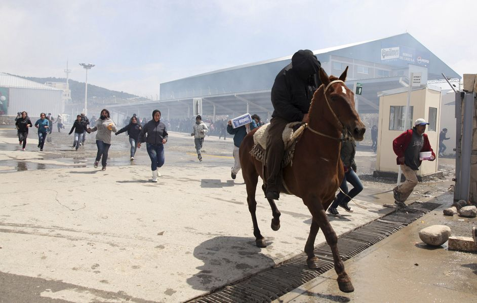 Un gruppo di persone scappa dopo aver saccheggiato i supermercati della stazione sciistica di San Carlos de Bariloche, in Argentina. (T. Reyes, Reuters/Contrasto)