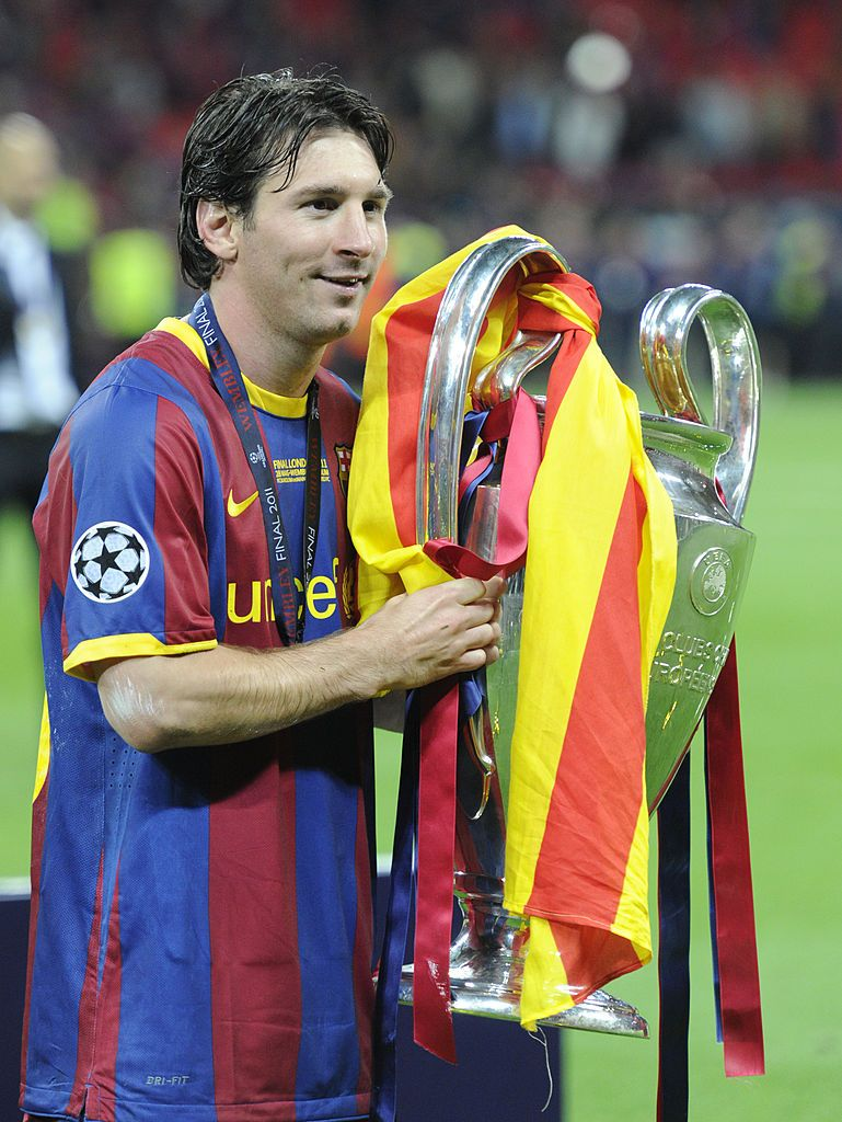 Lionel messi of barcelona celebrates with the trophy after
