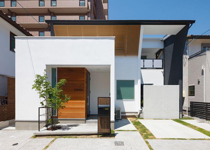 白と黒と木の茶の巧みな色使いが印象的な キューブ型の外観 住宅