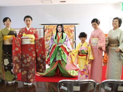 A woman dressed in junihitoe along side others dressed in modern kimono
