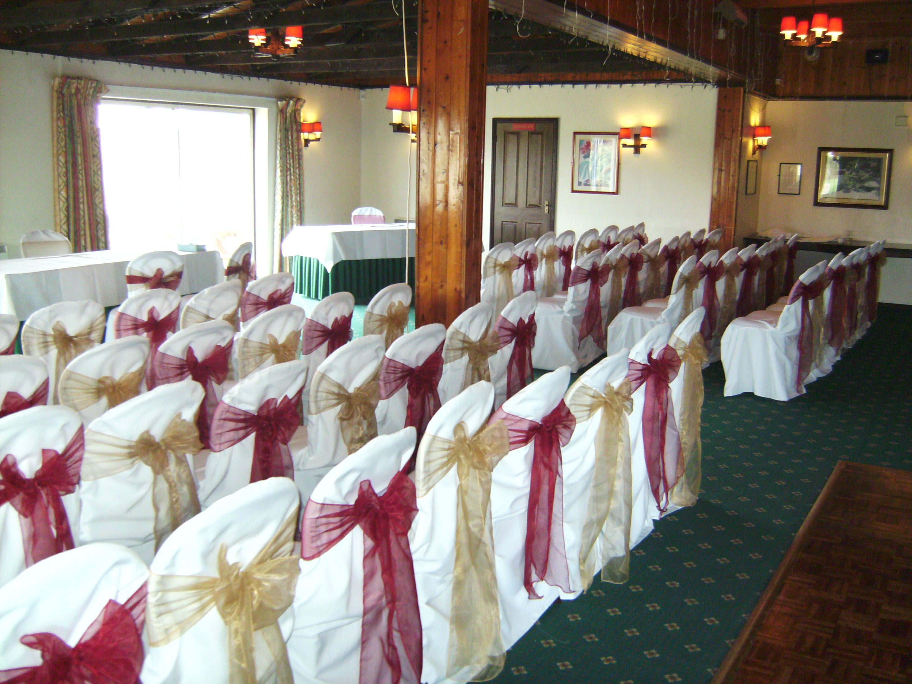 Alternating Burgundy And Gold Organza Bows On White Chair Covers