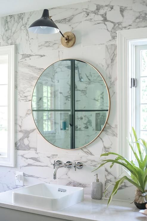 Gray And Gold Bathroom Boasts A Round Gold Vanity Mirror Mounted On White Marble Wall Tiles Illum Round Mirror Bathroom Bathroom Wallpaper Trends Gold Bathroom