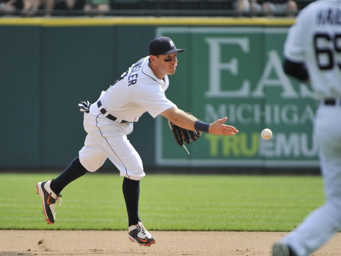 Tigers second baseman Ian Kinsler tosses the ball to