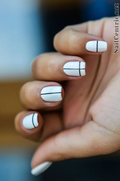 For a minimalist take on striped nail art, cross your white nails with  single black lines. See more at NailCentric. - 8 Subtle (and Oh-So Simple!) Nail Art Designs White Nails