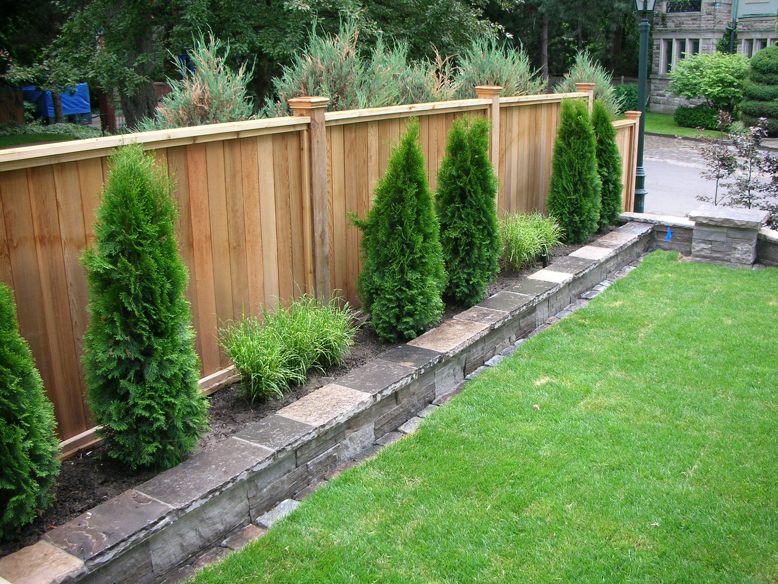 Fabulous example of the fence raised by mounting it on a for Backyard plant design ideas