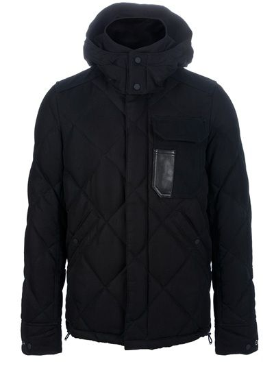 Black cotton blend feather down jacket from Junya Watanabe Comme des Garçons Man X Duvetica featuring a funnel neck, a hooded collar, a zip front fastening, a flap pocket with a contrasting patent leather print to the chest, two flap button pockets to the front, full length sleeves with a contrasting green checked print to the elbows and a quilted design to the rear.