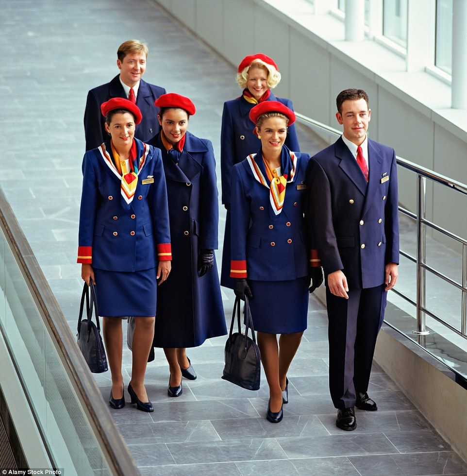 A group of brightly uniformed male and female cabin crew from Britannia Airways at an airport in 1996