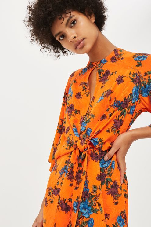 Warm up your wardrobe with this vibrant orange midi dress. In a colourful floral print, it features a knot front and keyhole slit, flared sleeves and an elegant asymmetric hem. Wear with kitten heels and a clutch bag.