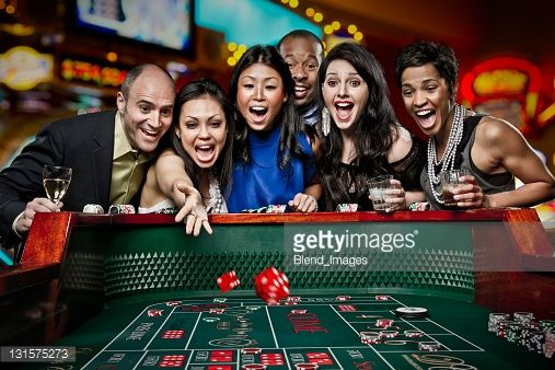Excited friends gambling at craps table in casino | Craps, Gambling, Casino
