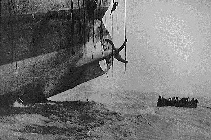 A last minute escape from a torpedoed ship. The ship's bow has already sunk into the waves, and her stern is slowly lifting out of the water. Men can be seen sliding down emergency escape ropes as the last lifeboat pulls away.