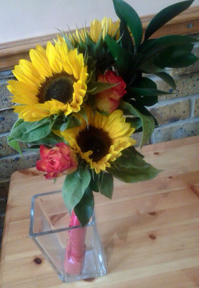 One of my designs. Over arm bridesmaids bouquet in autumnal shades with sunflowers.