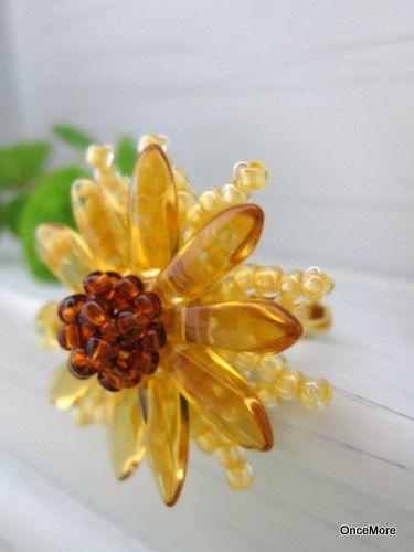 落ち着いたカラーの向日葵。花びらは二重仕立てになっています。外側はシードビーズをワイヤーで形作っています。ビーズフラワーの技巧で10枚の花びらを作りました。そ... ハンドメイド、手作り、手仕事品の通販・販売・購入ならCreema。