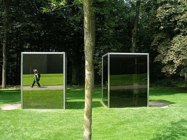 Dan Graham: Two adjacent pavilions door Dan Graham, 1982 / 2001. Museum Kröller Müller, Otterlo, de Hoge Veluwe. Het rechter gebouwtje heeft een transparant glazen dak waardoor mensen binnen van buitenaf gezien worden als de zon schijnt. Bij donker weer is het effect niet zichtbaar en spiegelt het glas.