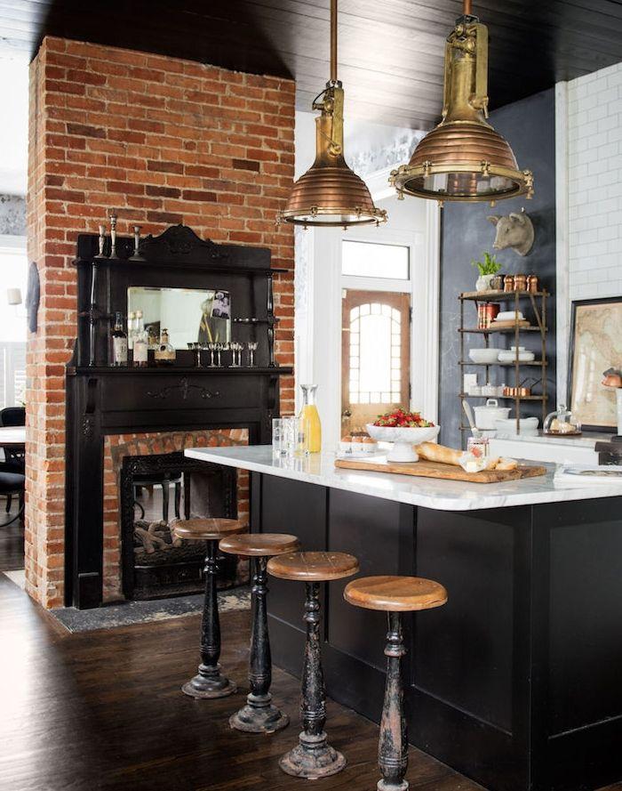 cuisine style campagne avec chemine en briques ilot central et pan de mur repeint de peinture ardoise plan de travail ilo en marbre