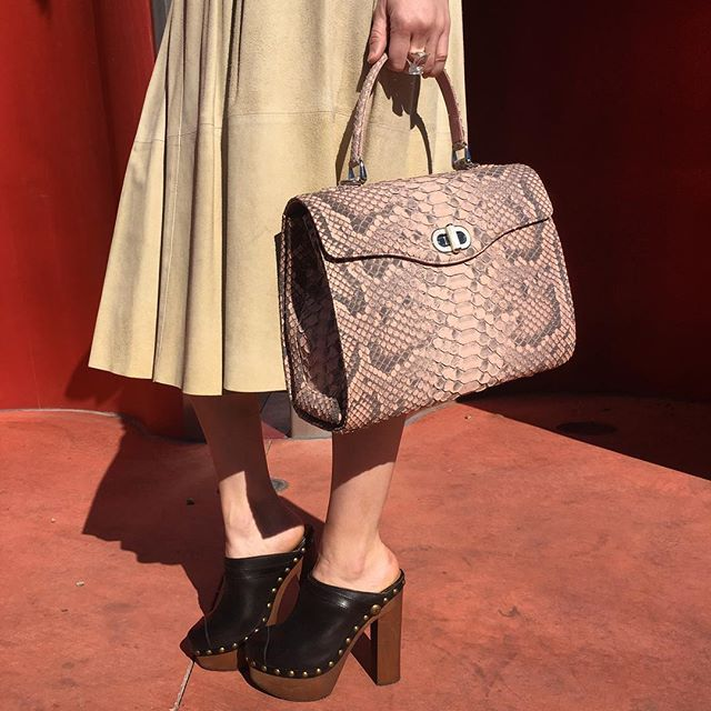 Add texture to your look with our luxurious Pink Python top handle bag. Chanel clogs available too! ...