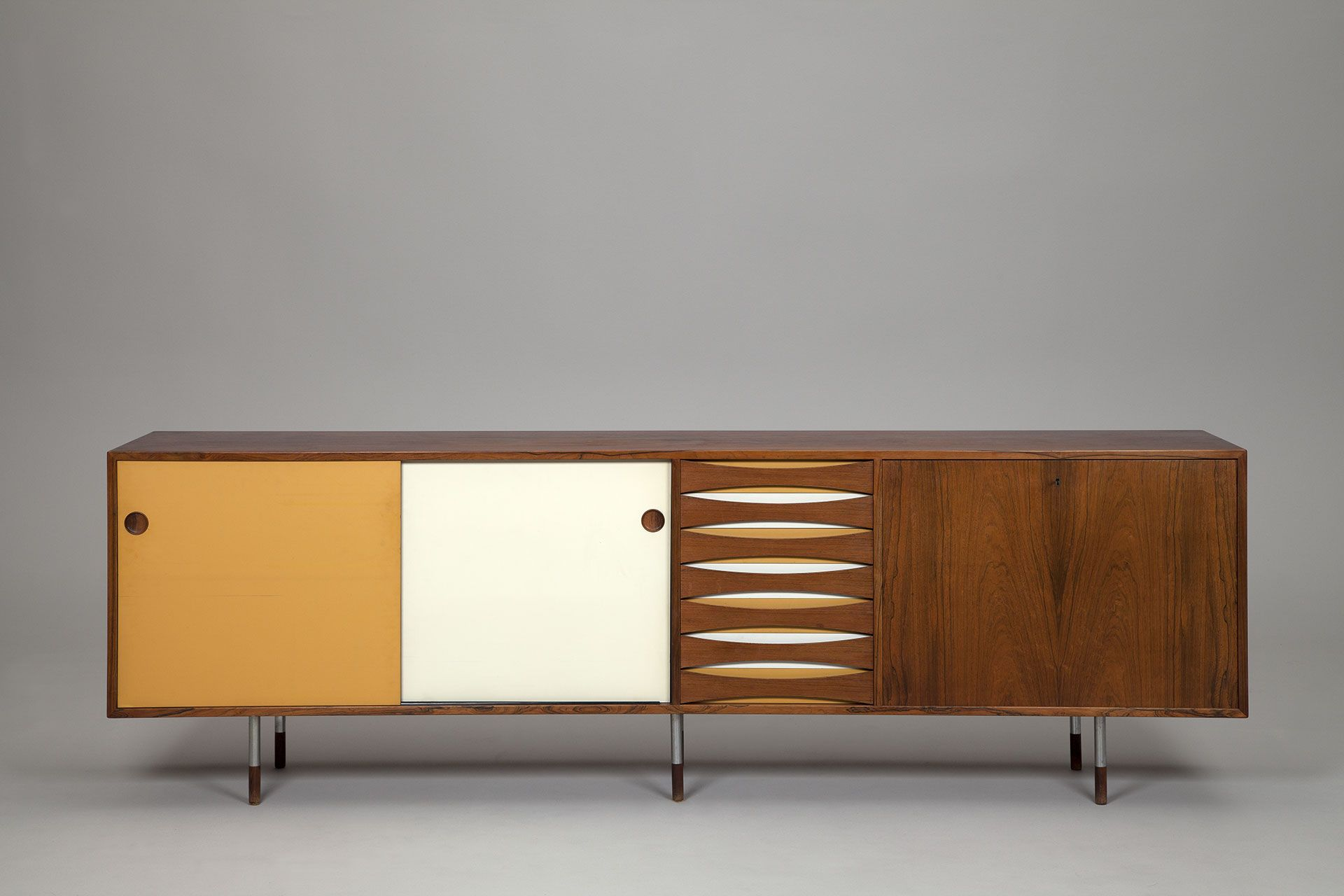 Vodder Sideboard. Rosewood cabinet with metal legs and rosewood feet. Drop leaf bar with laminated surface. Interior of light wood, adjustable shelves. Reversible doors in original painted white, yellow and rosewood back. Six drawers with background of original yellow, white and rosewood. Rosewood backside. Produced by Sibast A/S.