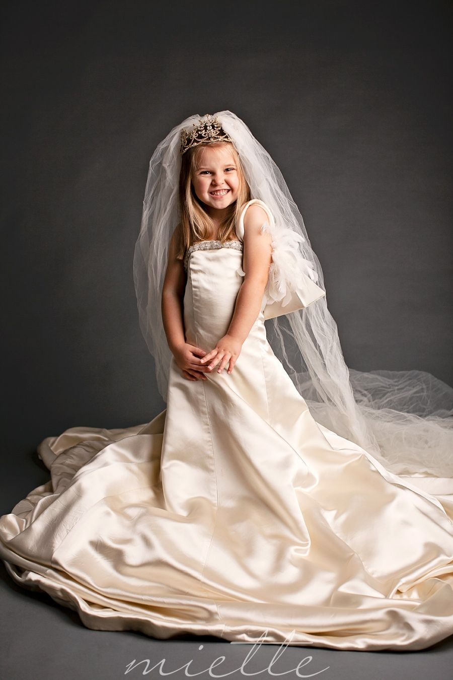 a little girl dresses up in her mother 39 s wedding dress