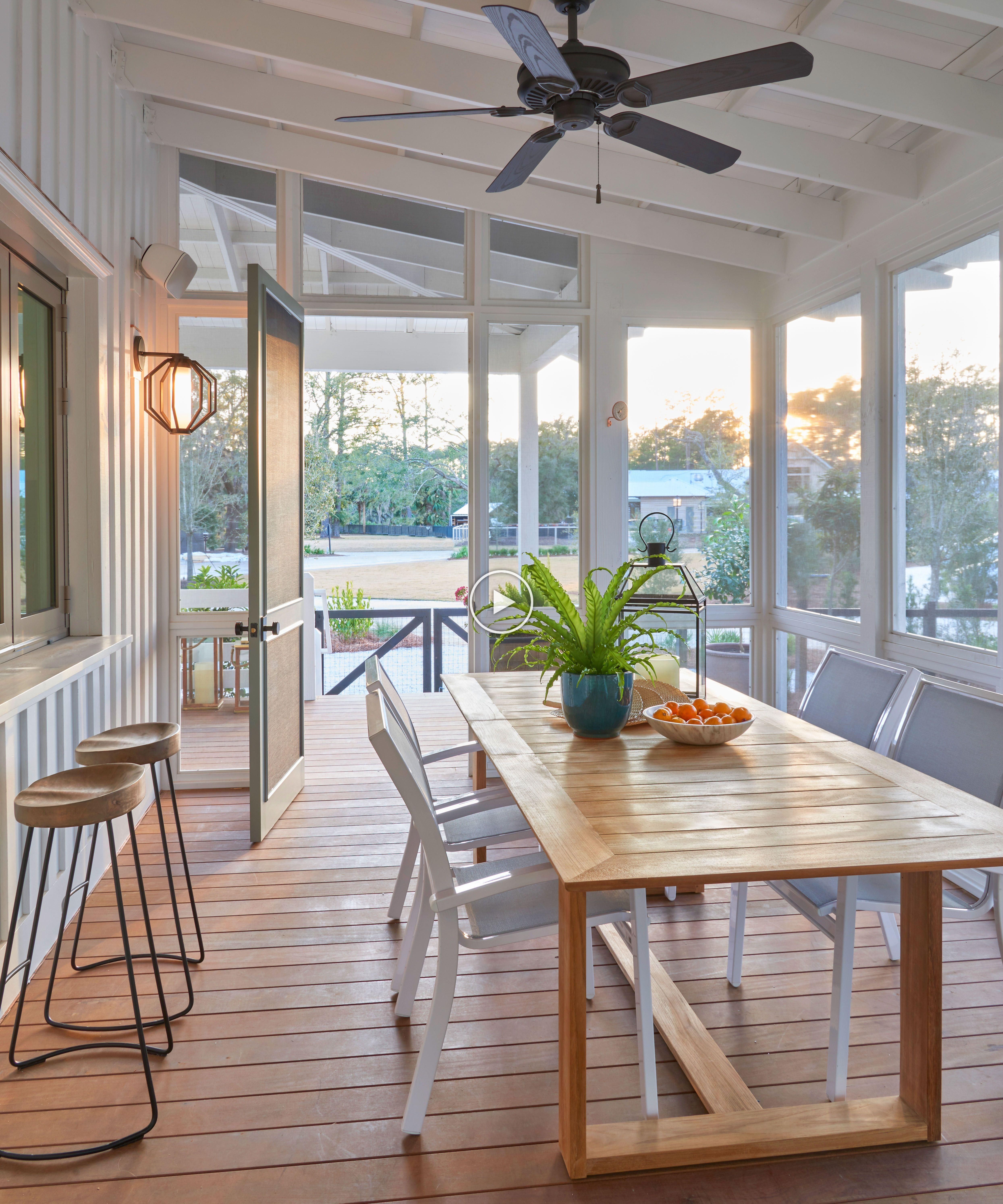 A screened-in porch with an exit to the outdoors and a firepit