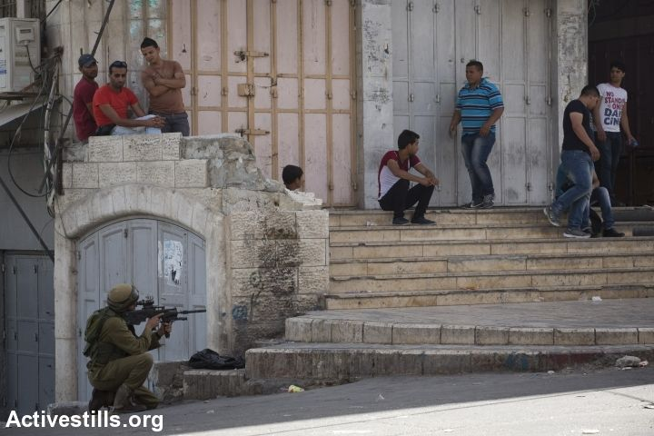 Palestinians look on as an Israeli soldier shoots rubber bullets during clashes with Palestinian youth in the West Bank city of Hebron, June 16, 2014. Israel broadened its search for three teenagers believed kidnapped by militants, arresting over over 200 Palestinians while imposing a tight closure on the southern West Bank city. (Photo: Oren Ziv/Activestills.org)