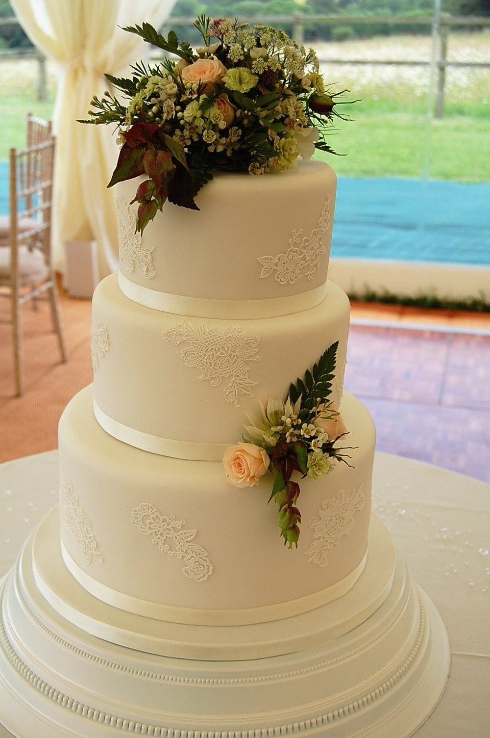 Three tier wedding cake with lace decoration. Each tier is a ...