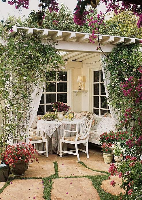 Patio with table, chairs and bench. Love the curtains and flowers ...