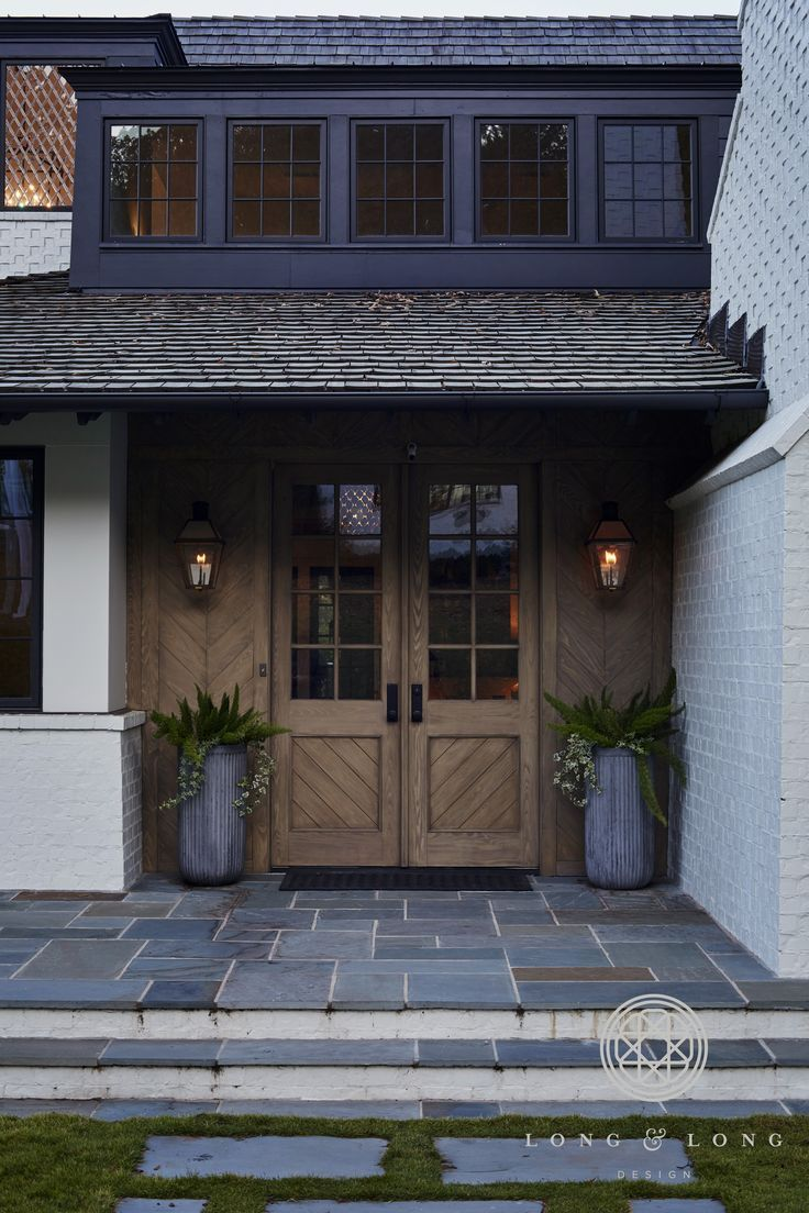 Wooden front door with navy blue and white exterior and dark roof