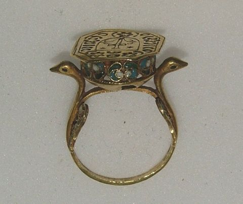 Eastern Europe.  17th century.  Gold signet ring, the octagonal bezel engraved with a shield and a cross between two stars and two lilies and surrounded by a border of stars, crescents and other shapes, the hoop formed into a bird's head and neck at the shoulders with lateral wings of cloisonné enamel in blue, green and white