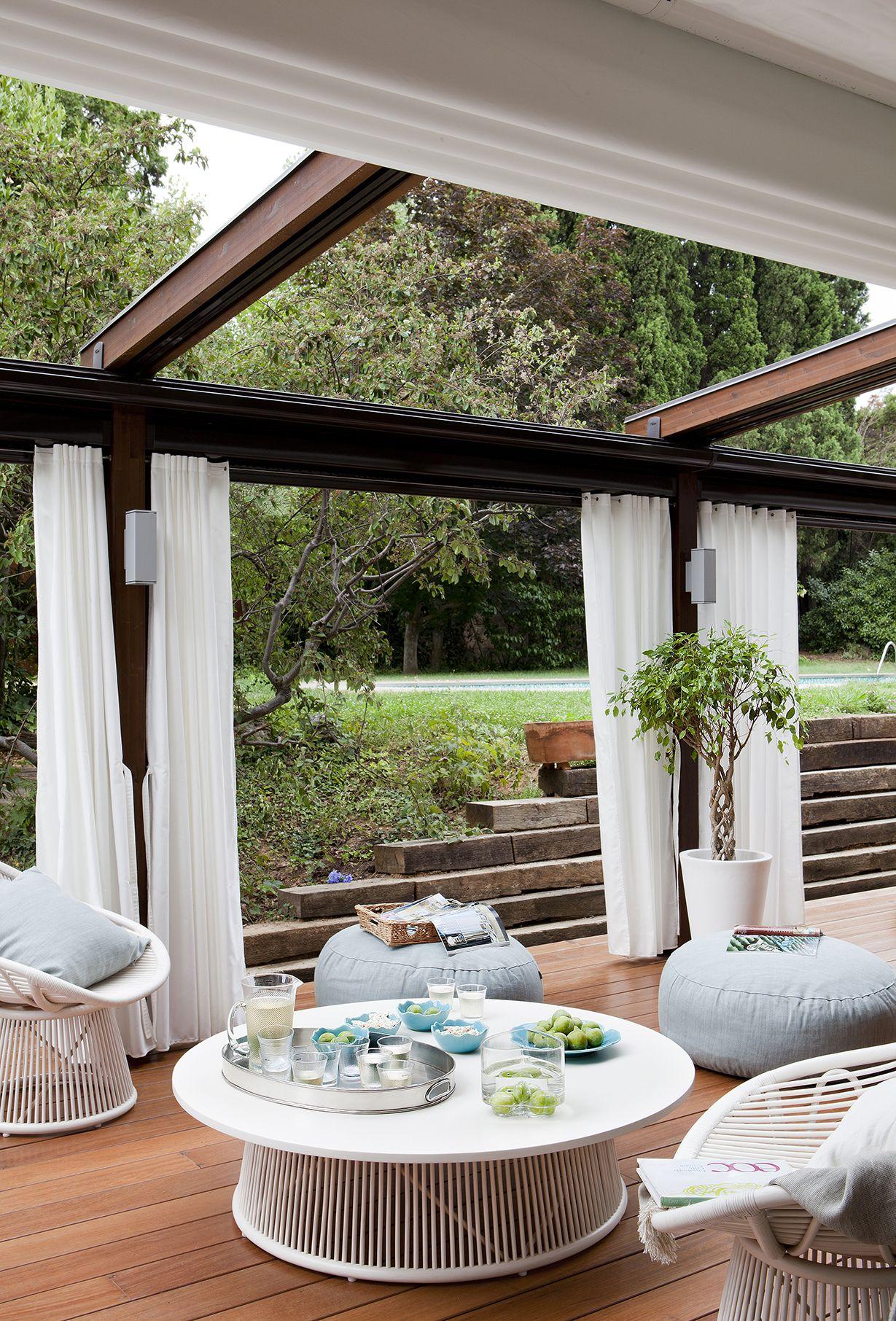 Salón exterior de verano con pérgola, cortinas, mesa de centro ...