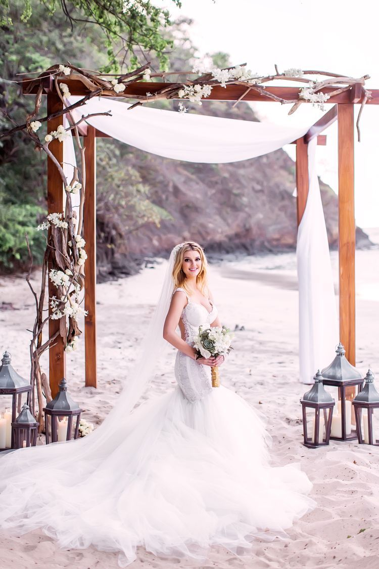 3fd6318100b4 In love with this mermaid wedding dress and wedding arch. This is such a  beautiful destination wedding idea.