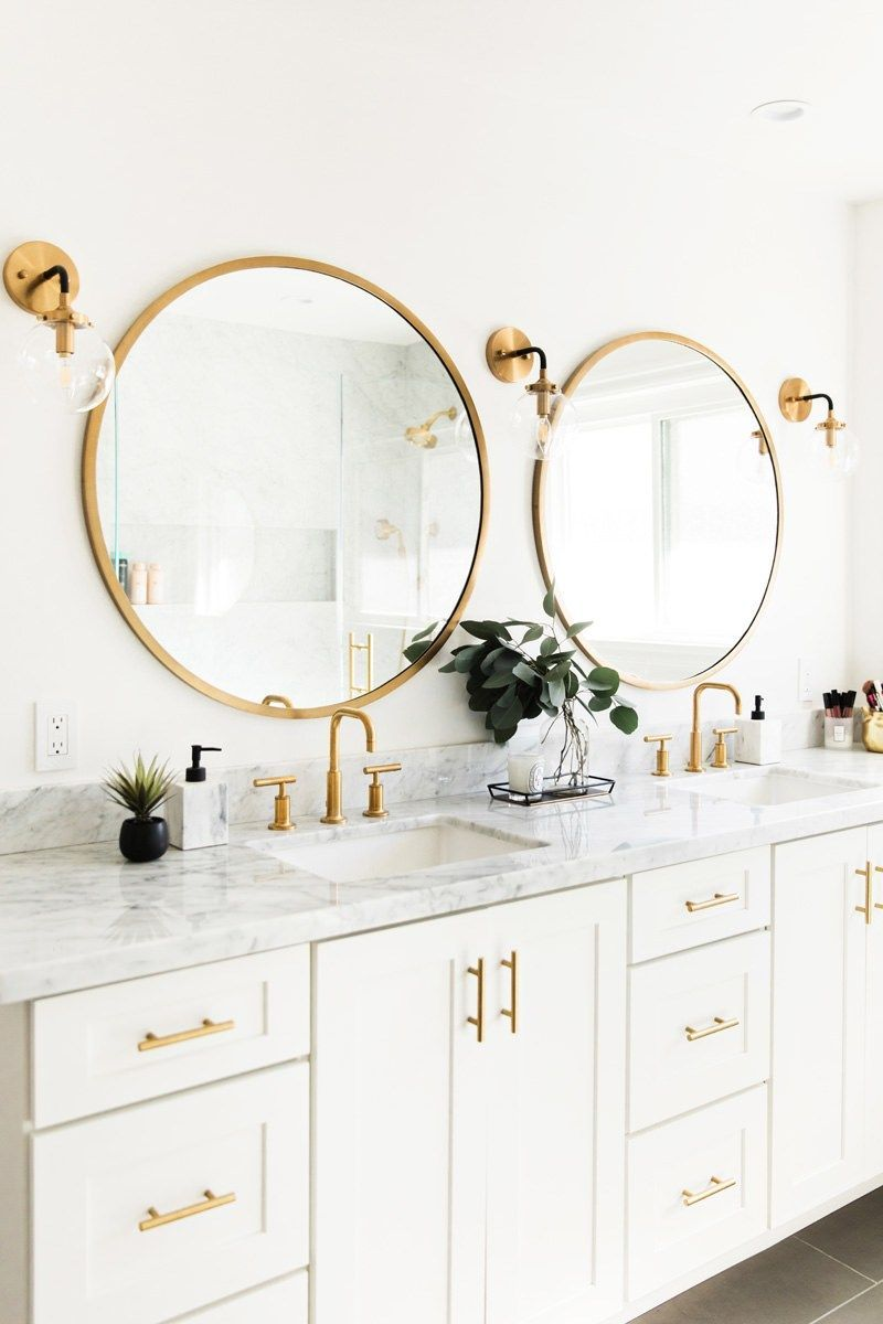 Photo of Like the white cabinets, marble tops, gold circular mirrors, light fixtures