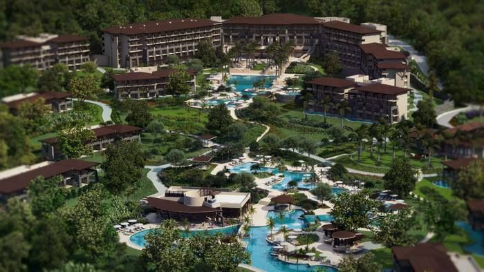 Beautiful aerial view of Dreams Las Mareas Costa Rica, a luxury resort surrounded by green jungle and blue waters.