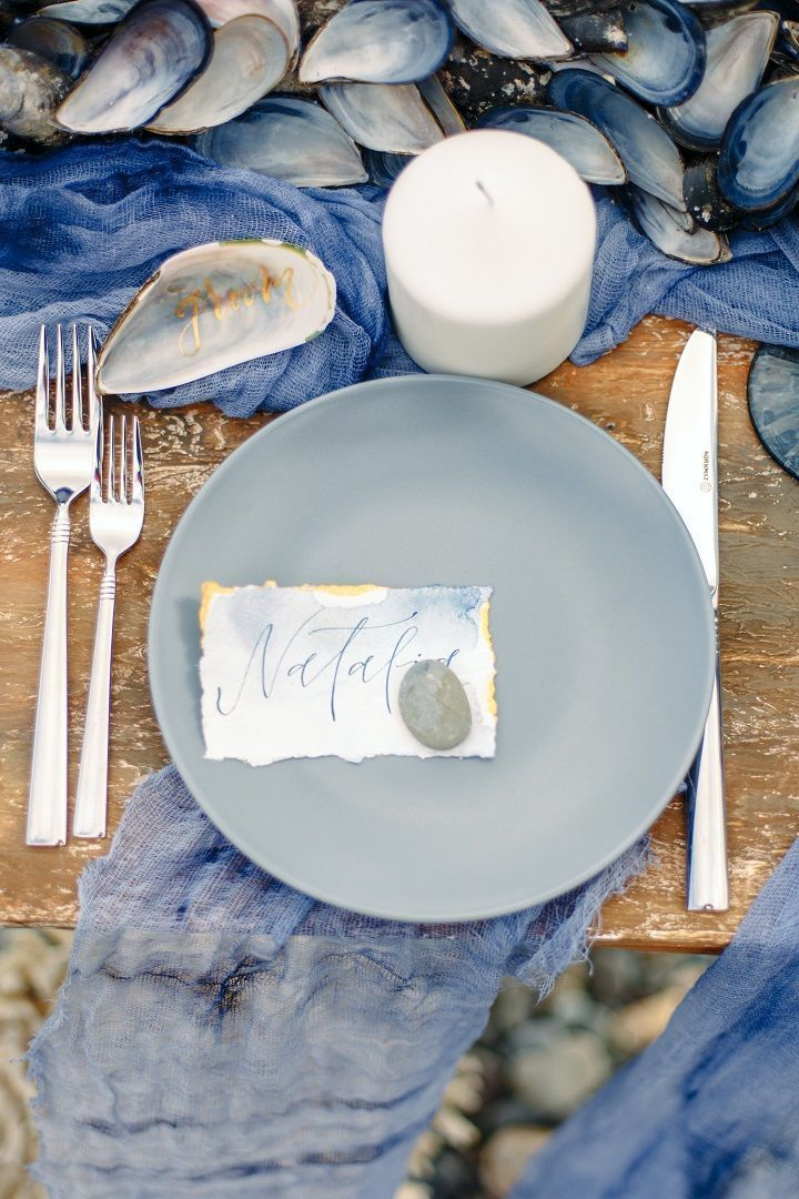 Gold calligraphy written on mussel shell as seating name   Beach wedding table setting in shades of ocean blue   fabmood.com #weddingtable #weddingtablescape #tablesetting #beachwedding #beachtablescape #oceanblue #mistyblue #mistygrey