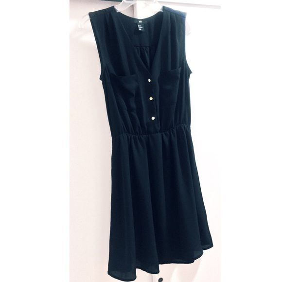 Amazing LBD This like-new LBD is a flattering v-neck with gold accent buttons. There are two pockets on the chest-great detailing! The waist is elastic so it's super flattering. Can be worn on its own but it's always great for layering and tights. A go-to dress for any occasion! H&M Dresses