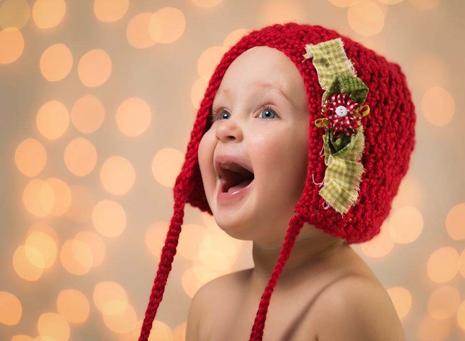 Blurring the background. Child in red bonnett with twinkling lights in the background by Kate Luber