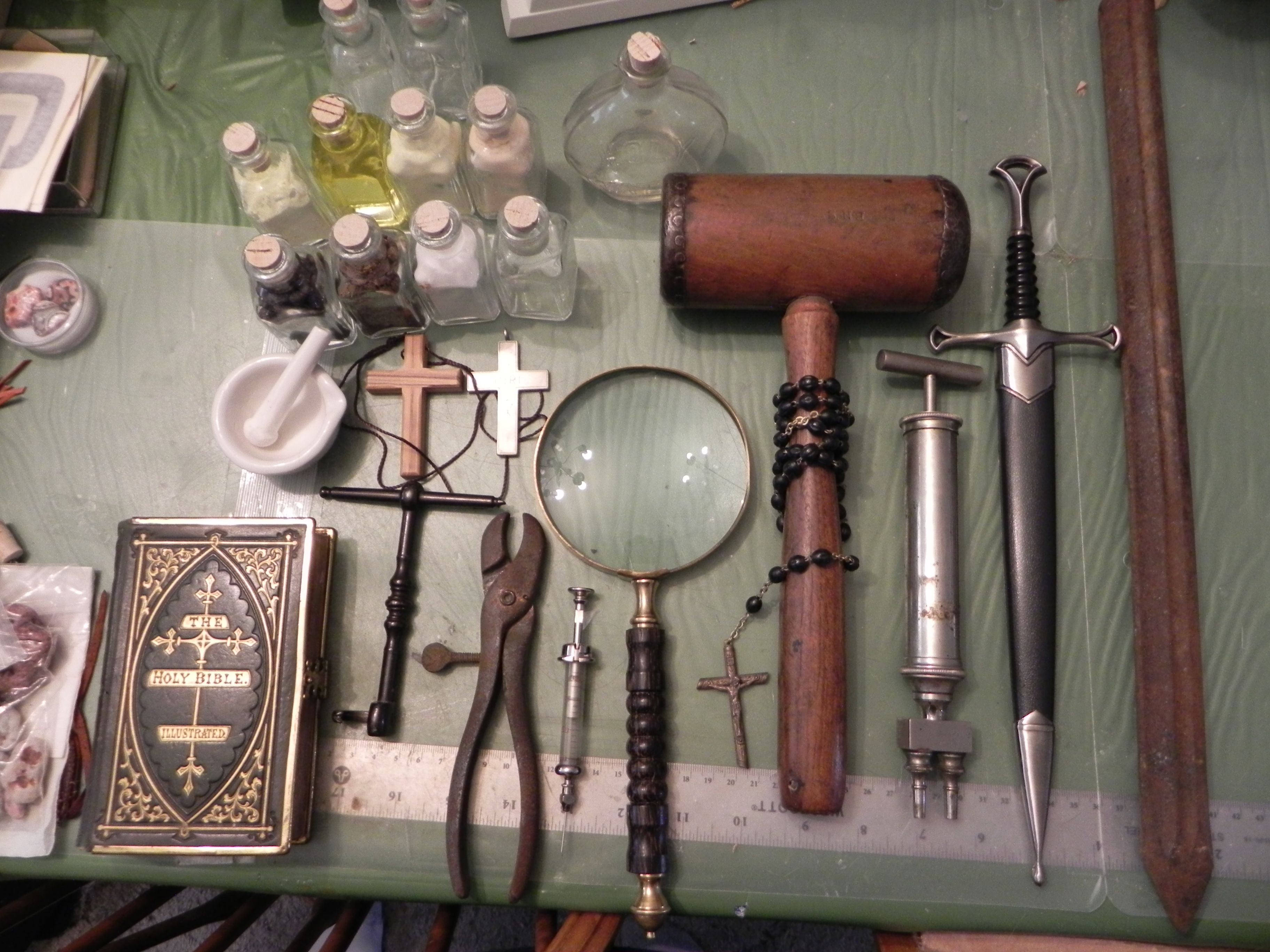 Some of the potential parts.  1800's Bible, silver cross, olive (holy) wood cross, two types of tooth-pulling tools, rosary, lense, mortar and pestle, dagger (may change it), 1800's hypodermic, lovely old mallet, bottles of *authentic* remedies that are chemically correct.  More to come!
