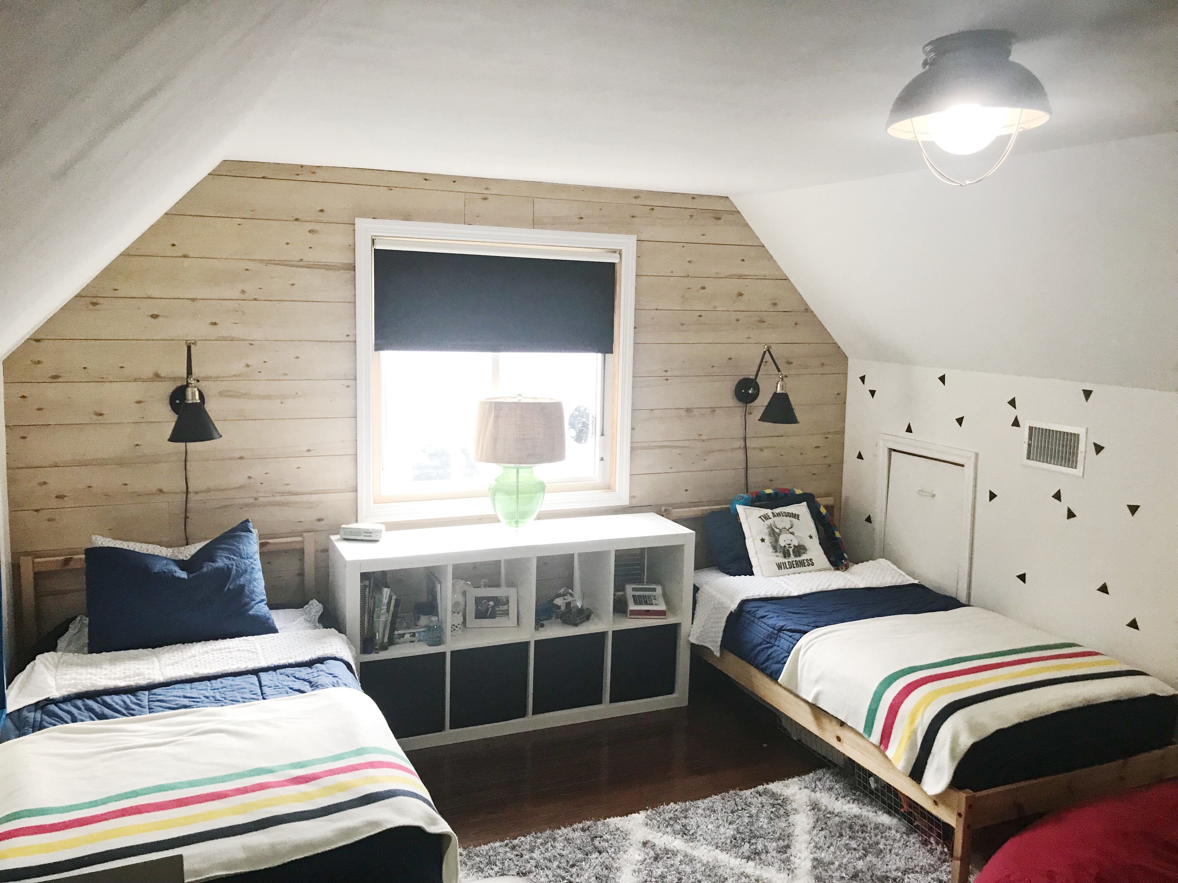 Little boys Wilderness Bedroom. Two twin beds with a classic wall mounted light fixture and of could a jumbo red bean bag and oh course some Hudson Bay Striped Throws over Beddys Bedding
