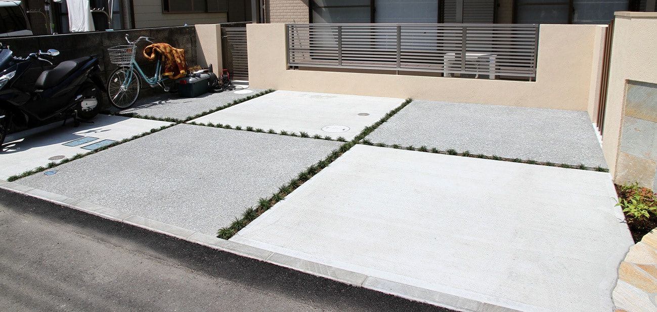 一般的な土間コンクリート1色ですが 2つの仕上げを組み合わせて2色のデザインにしています 白い部分は一般的な刷毛引き仕上げ グレーの部分はコンクリート洗い出し仕上げという工法を採用しています この2色を組み合わせることで 市松模様に仕上がりました 単調に