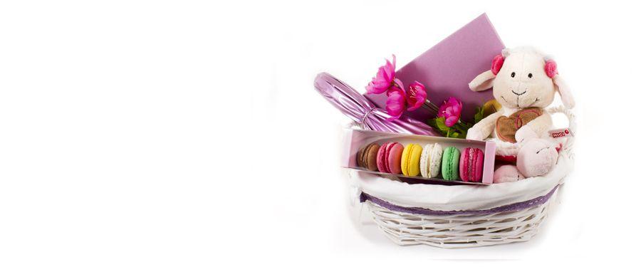 Cesta regalo de nacimiento rosa. Cesta de mimbre forrada con tela, cava Vallformosa Brut Nature, caja de bombones artesanos de Ascaso (20 unidades), caja macarons artesanos de Ascaso y peluche Nici con lazos rosas.