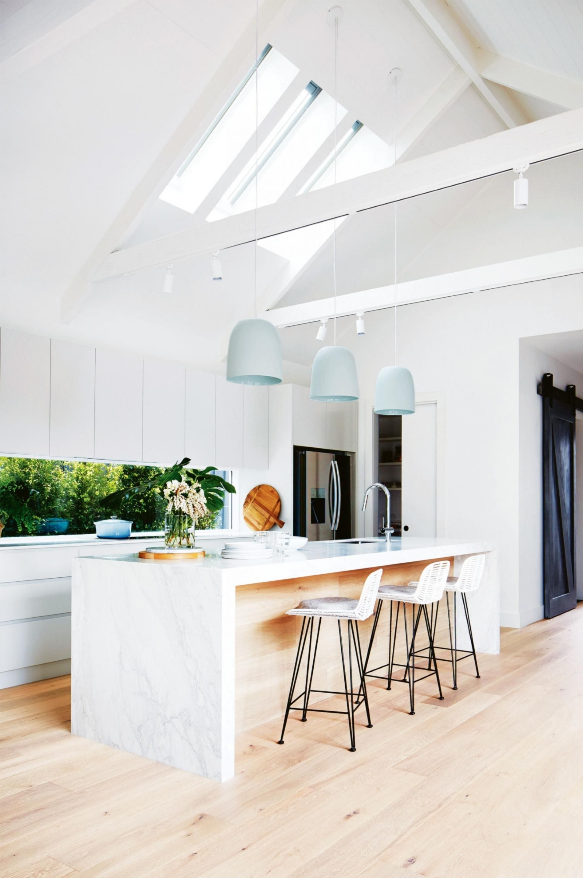 All white minimalist kitchen with a waterfall marble island light ...