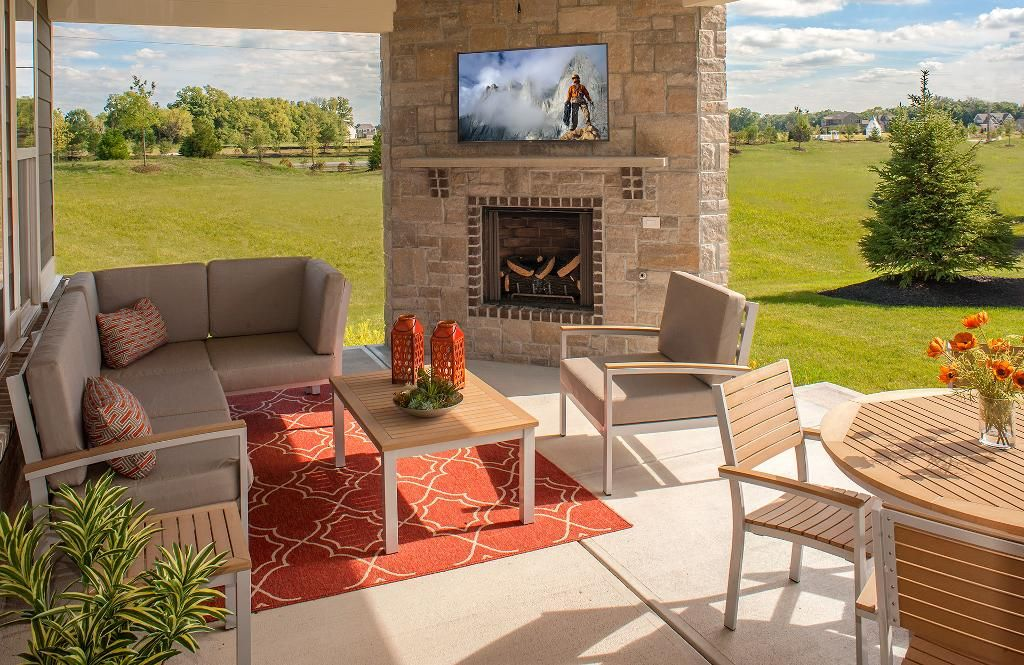 Outdoor patio living with a stone fireplace and TV; The Ash Lawn ...