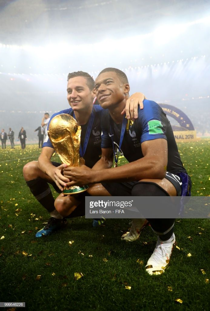 Florian Thauvin and Kylian Mbappe of France celebrate victory with the World Cup trophy following the 2018 FIFA World Cup Final between France and Croatia at Luzhniki Stadium on July 15, 2018 in Moscow, Russia.