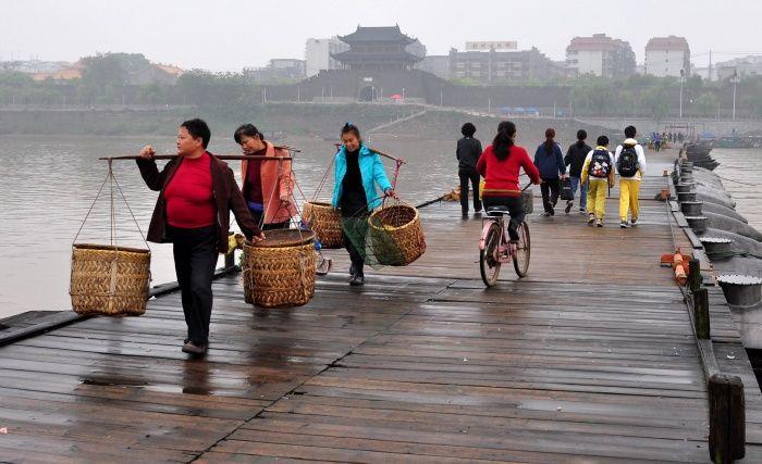 Des passants traversent un pont flottant ancien sur le fleuve Gongjiang dans la ville de Ganzhou de la province orientale du Jiangxi, le 1er avril 2013