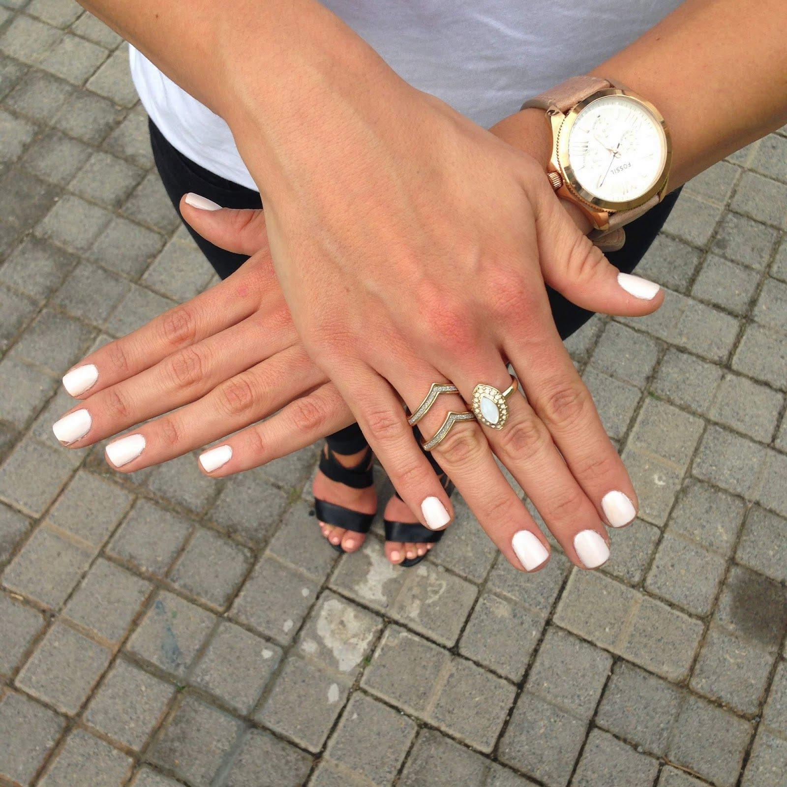 Nude white nails and gold watch.
