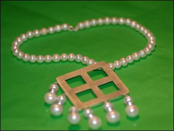 Collar de perlas del que cuelga una pieza de plata con forma ...
