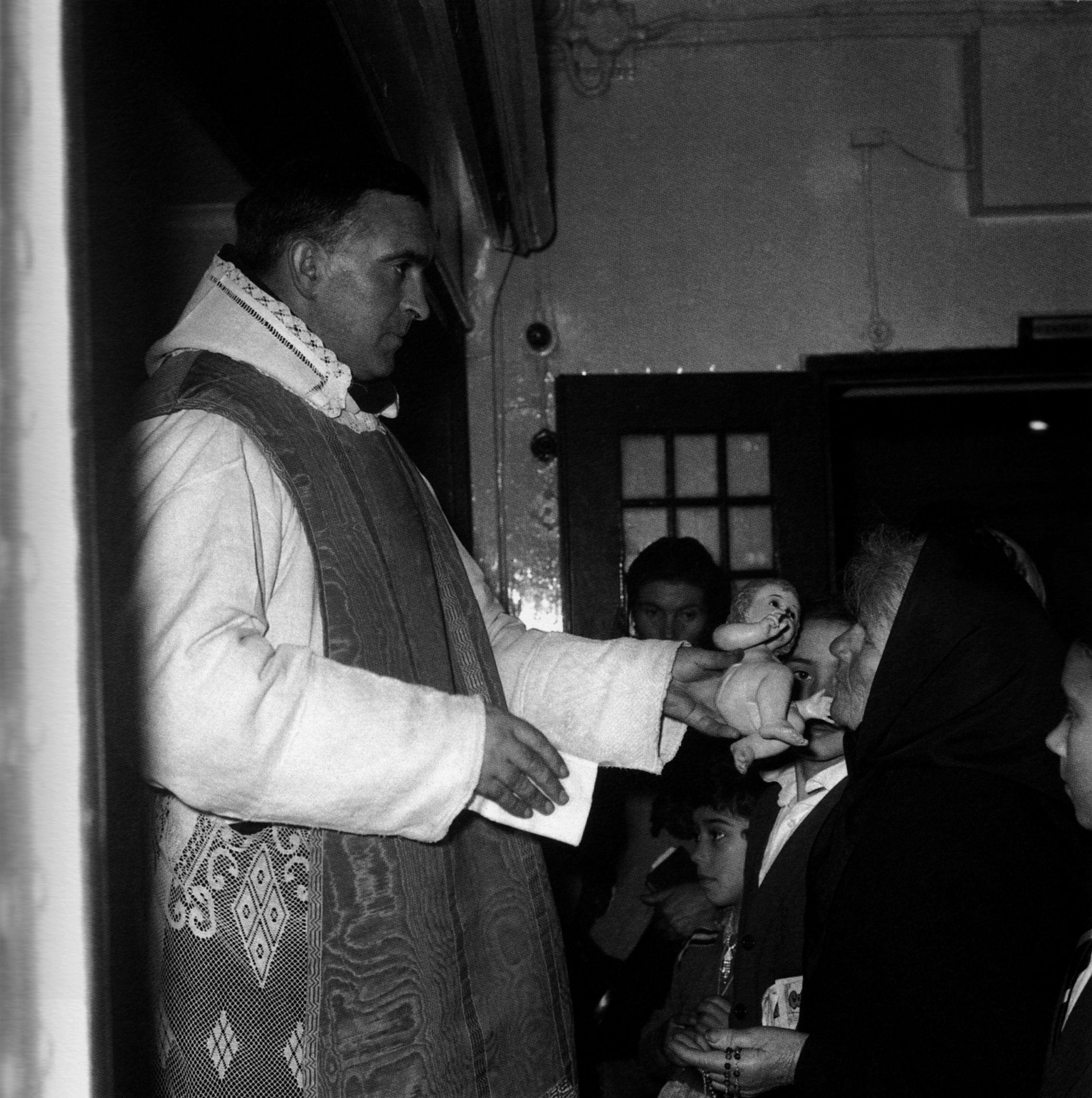 O sacerdote dálles a bicar a unhas emigrantes a figuriña do neno Xesús. A Coruña, 1963
