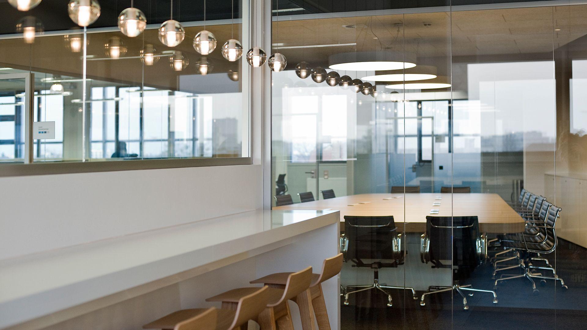 Empfangsbereich mit einer Sitztreppe aus Holz und im Kontrast dazu eine schwarze Theke fice McCANN Advertising Agency Berlin