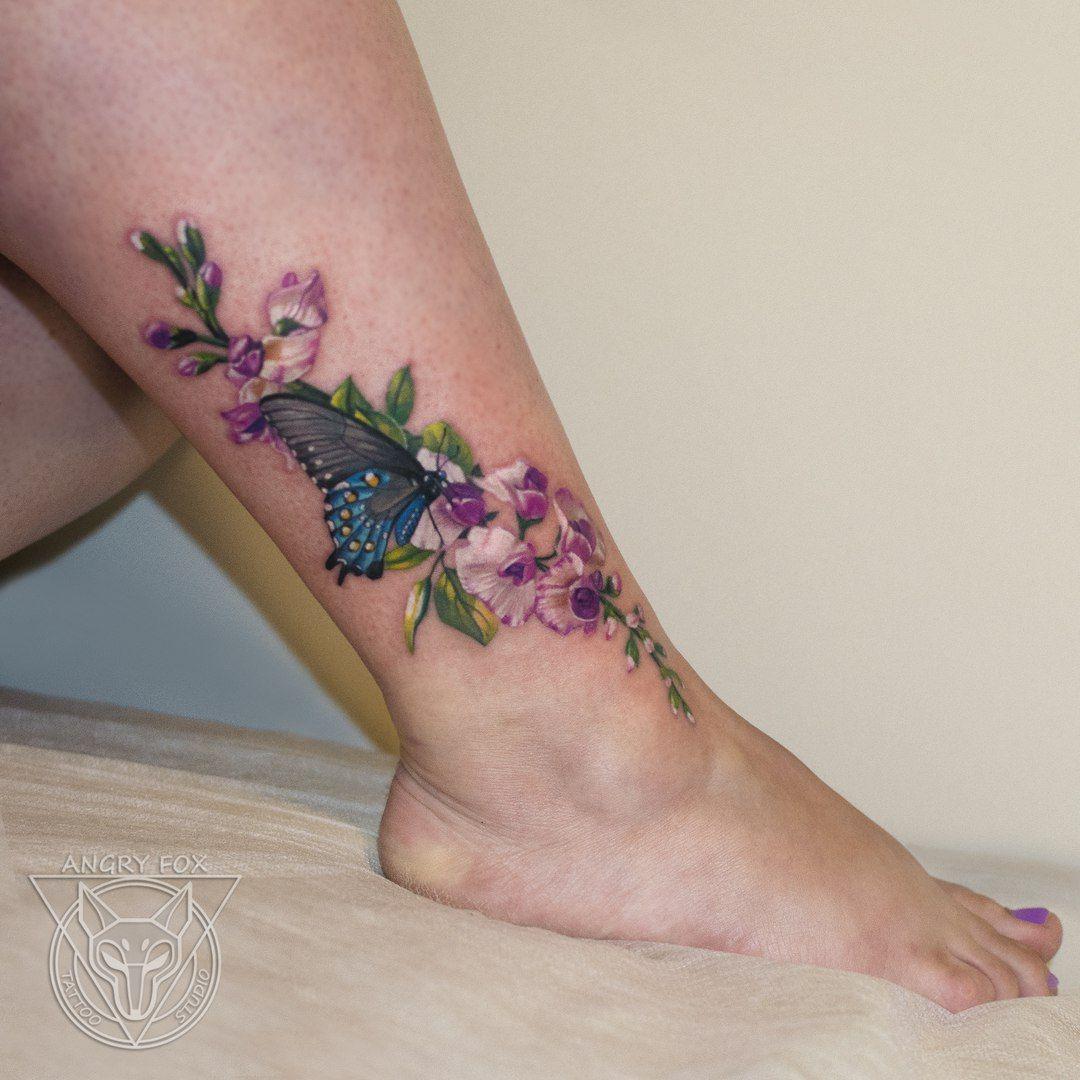 цветы белые орхидеи и синяя бабочка тату на ноге у девушки